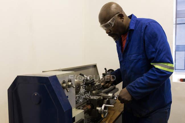 Forgeron attentif utilisant la machine en atelier — Photo de stock