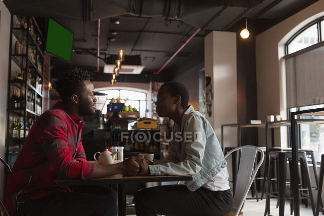 Side view of couple interacting with each other in cafe — Stock Photo