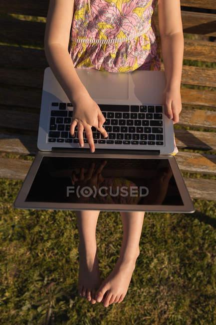 Kopf von Mädchen mit Laptop im Garten an einem sonnigen Tag — Stockfoto