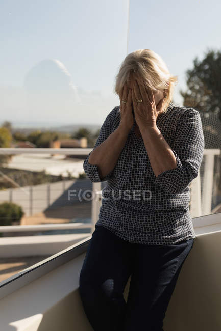 Worried woman covering her face on terrace — Stock Photo