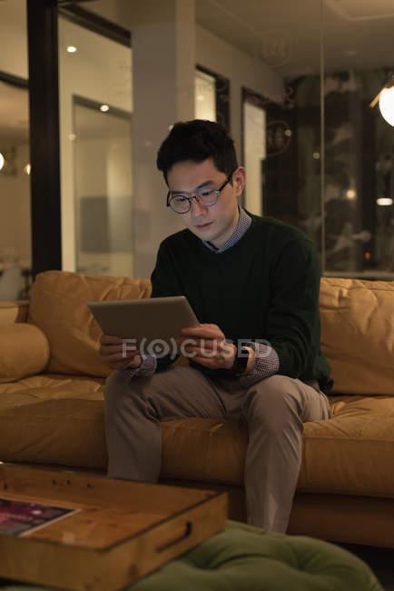 Homem de negócios concentrado sentado no sofá e usando tablet digital — Fotografia de Stock