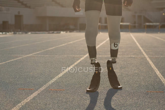 Low section of disabled athlete standing on a running track — Stock Photo