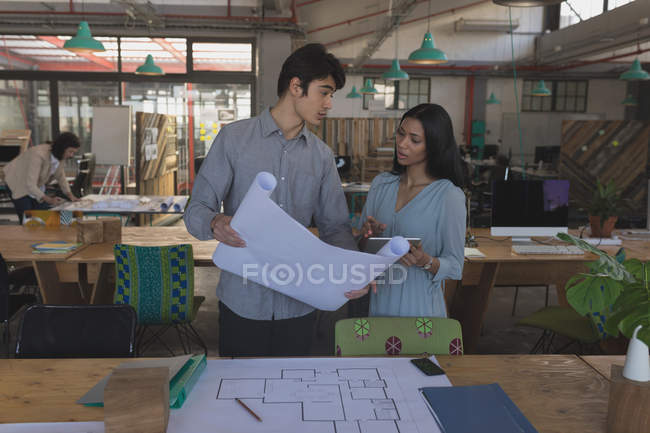 Executives Discussing Over Blueprint In Office Real Estate Mid