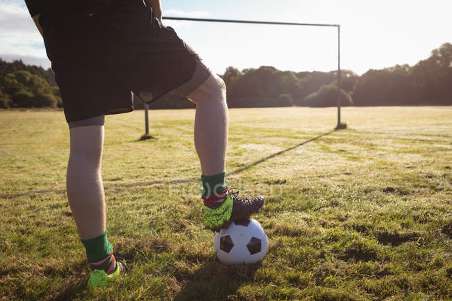 Unterteil des Fußballers, der mit dem Ball auf dem Feld steht — Stockfoto