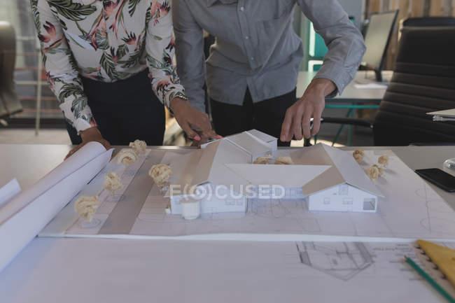 Sezione media di dirigenti che lavorano su modello di casa in ufficio — Foto stock