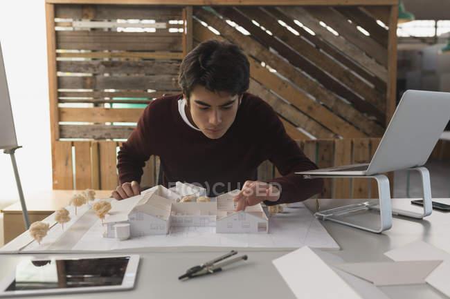 Hombre Ejecutivo trabajando en la casa modelo en la oficina - foto de stock