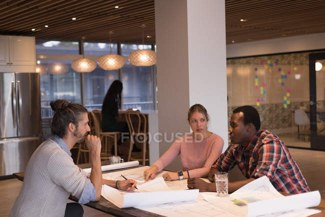 Business people discussing blueprints in the office — Stock Photo