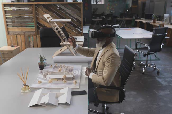 Homme exécutif utilisant casque de réalité virtuelle à table dans le bureau — Photo de stock