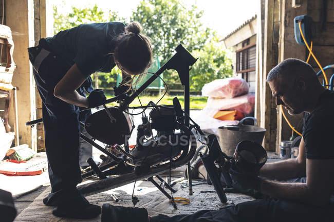 Чоловічий і жіночий mechanicians, ремонт мотоцикл в ремонт гаража — стокове фото