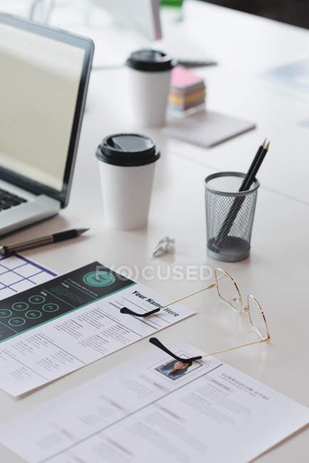 Portátil, o documento e o escritório dos artigos de papelaria na secretária no escritório — Fotografia de Stock