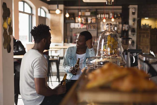 Couple en interaction avec l'autre tout en ayant la bière au café — Photo de stock