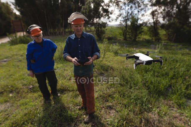 Dois lenhadores operando drone na floresta — Fotografia de Stock