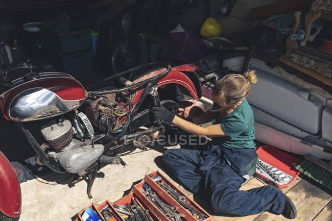 Висока кут зору жіночий механік ремонту мотоцикл в гаражі — стокове фото