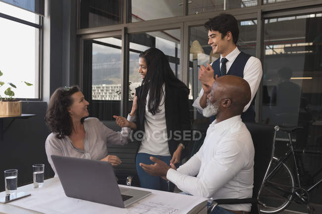 Business executives interacting with each other in office — Stock Photo