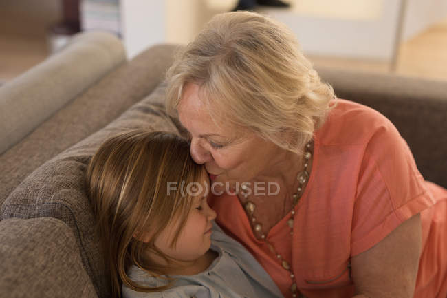 Grandmother kissing her granddaughter in living room at home — Stock Photo