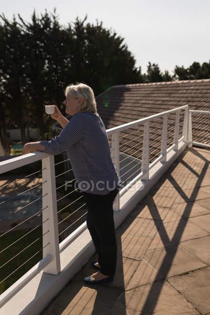 Thoughtful senior woman having coffee on terrace — Stock Photo