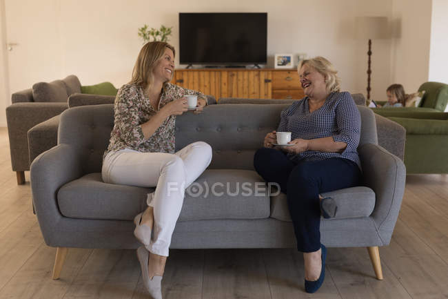 Mother and daughter interacting with each other while having coffee in living room at home — Stock Photo