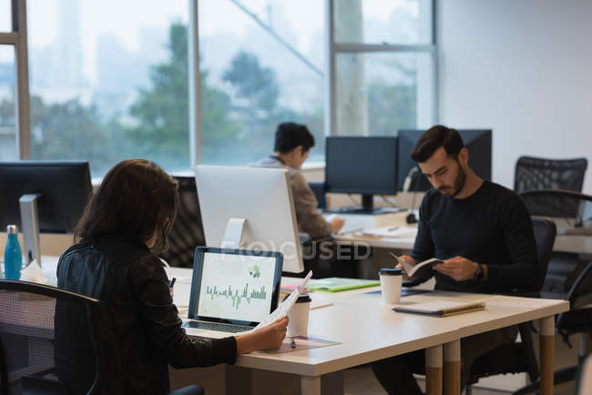 Concentrated businessman reviewing the sales graph on laptop and colleagues busy working — Stock Photo