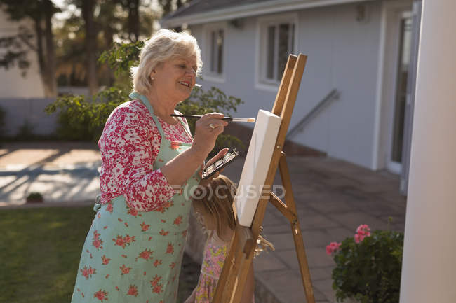 Side view of senior woman painting on canvas in the garden — Stock Photo