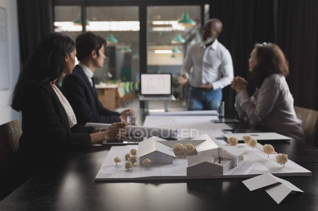 House model in conference room at office and business people — Stock Photo