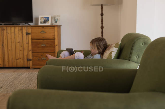 Girl using digital tablet in living room at home — Stock Photo