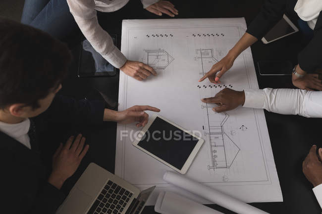 Business executives discussing over a blue print at office — Stock Photo