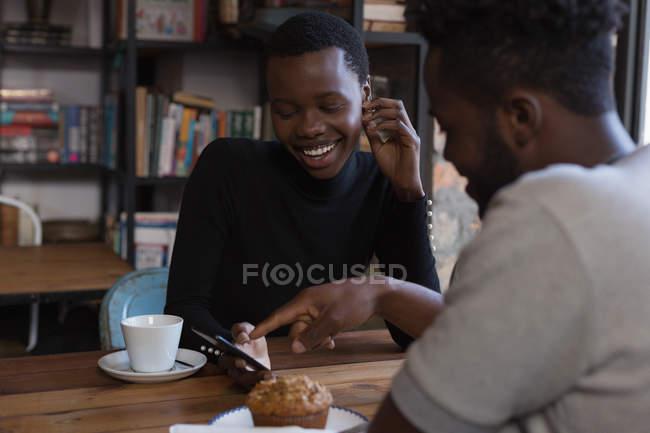 Счастливая пара обсуждения по мобильному телефону в кафе — стоковое фото