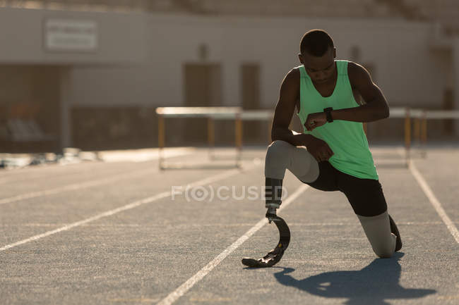 Male disabled athlete checking time on a running track — Stock Photo