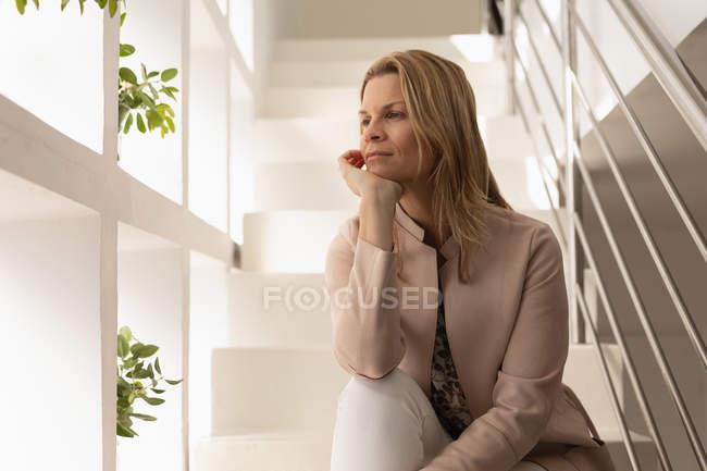 Задумчивая женщина отдыхает на лестнице дома — стоковое фото