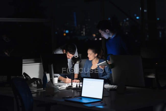 Three business people working on laptop in office during nighttime — Stock Photo