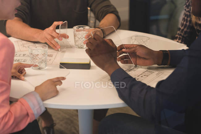 Mid section of business people using invisible digital tablets in meeting — Stock Photo