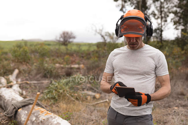 Lumberjack using digital tablet in forest — Stock Photo