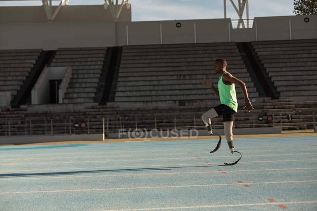 Side view of disabled athlete standing on a running track — Stock Photo