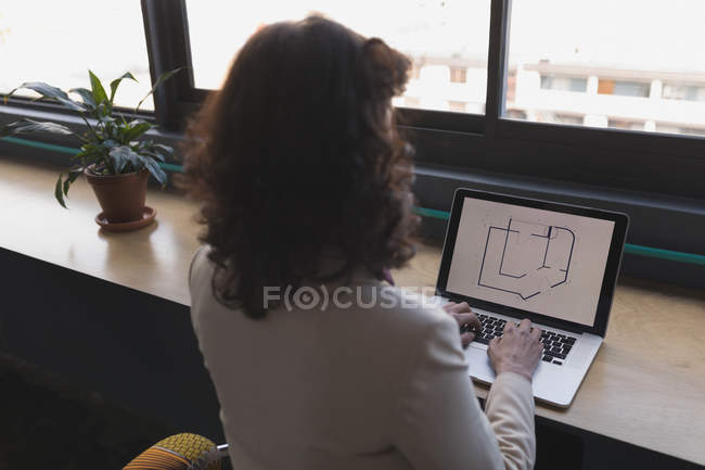 Female executive working on laptop at table in office — Stock Photo