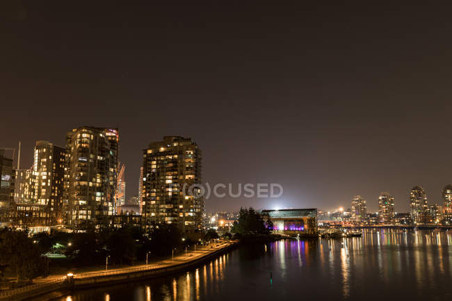 Modern downtown with light trail and river — Stock Photo