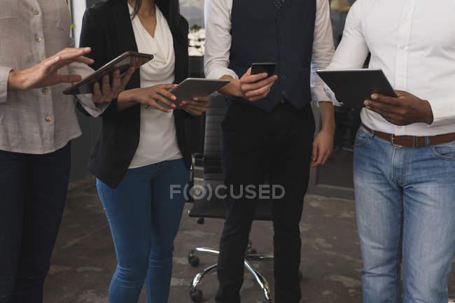 Media sezione di uomini d'affari che utilizzano tablet digitali invisibili in riunione — Foto stock