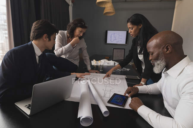 Dirigenti d'azienda che discutono su una stampa blu in ufficio — Foto stock