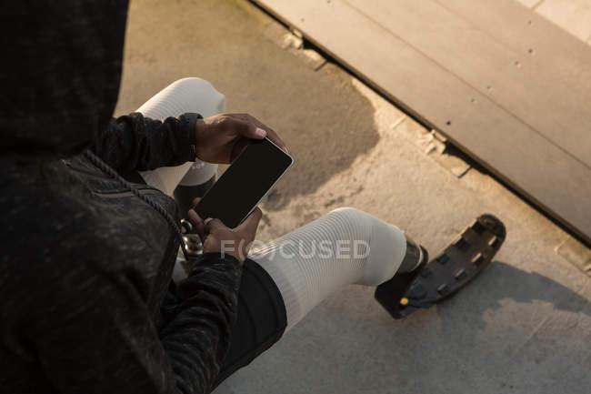 Высокий угол обзора спортсмена-инвалида с помощью мобильного телефона на спортивном объекте — стоковое фото