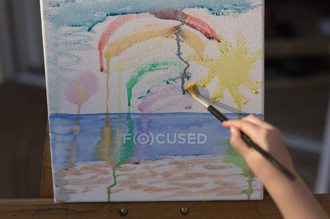 Close-up of girl painting on canvas in the porch — Stock Photo