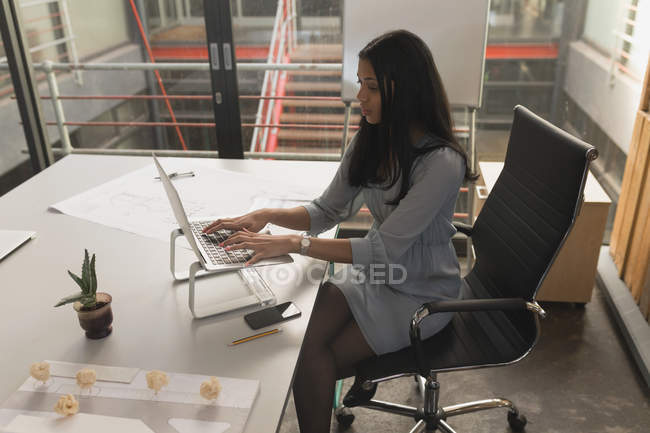 Female executive working on laptop in office — Stock Photo