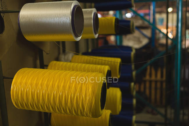 Close-up of thread roll arranged in rack at rope making industry — Stock Photo