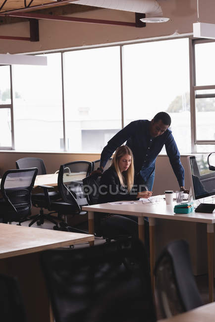 Concentrated businessman and businesswoman working on the sketches in the office — Stock Photo