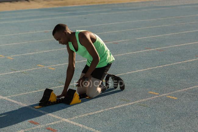 Athlète handicapé se préparant pour la course sur une piste de course — Photo de stock