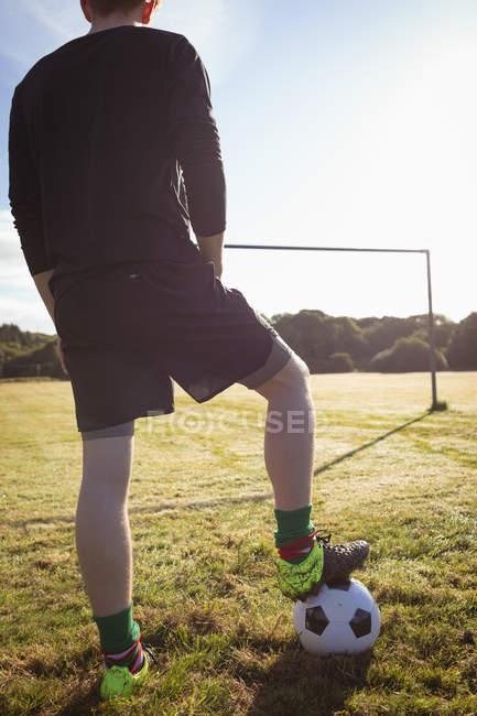 Niedrige Abschnitt des Fußballspielers stehend mit Fußball im Feld — Stockfoto
