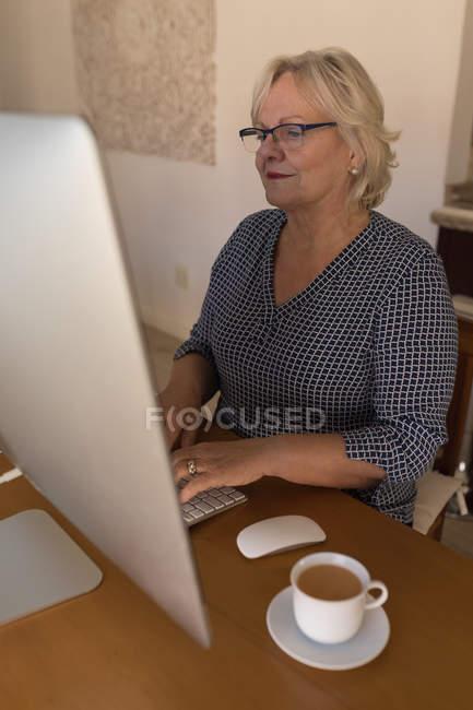 Femme âgée travaillant sur ordinateur à la maison — Photo de stock