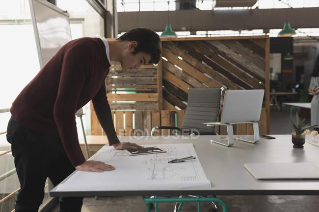 Exécutif mâle à l'aide de tablette numérique tout en travaillant sur le plan directeur au bureau — Photo de stock
