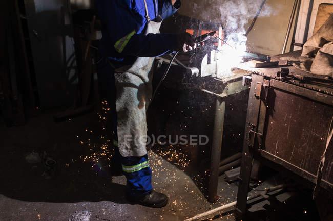 Низкий сечение кузнеца с помощью сварочной горелки в мастерской — стоковое фото