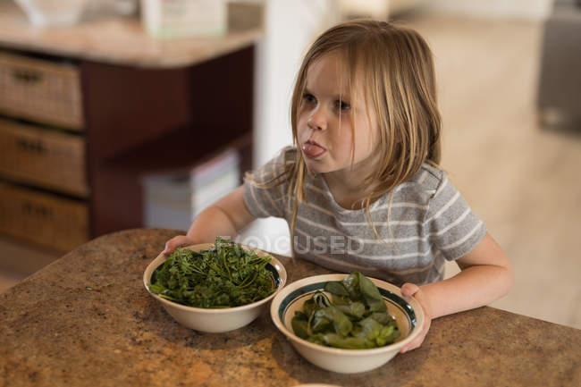 Girl holding bowl of green vegetables in kitchen at home — Stock Photo