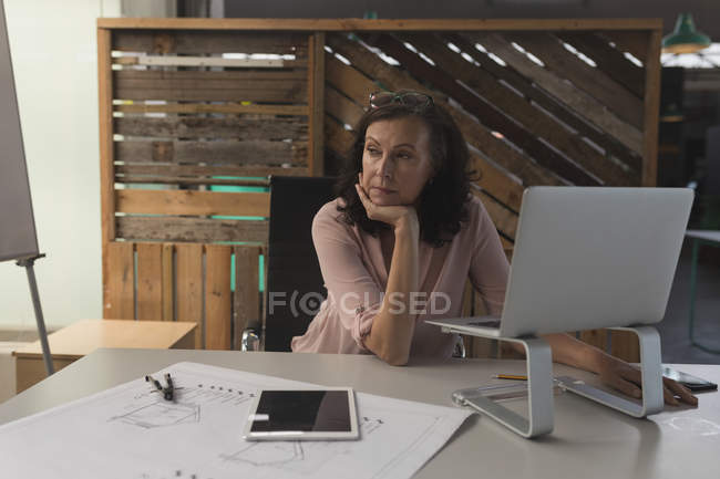 Thoughtful female executive sitting at table in office — Stock Photo