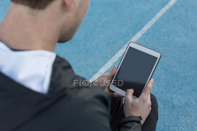 Primer plano del atleta utilizando tableta digital en el lugar de los deportes - foto de stock